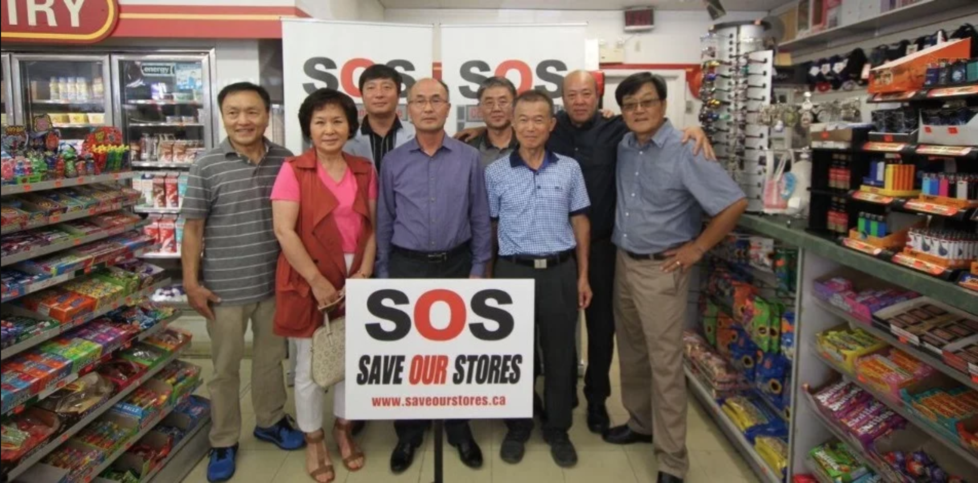 OKBA store owners standing in a convenience store with an SOS sign